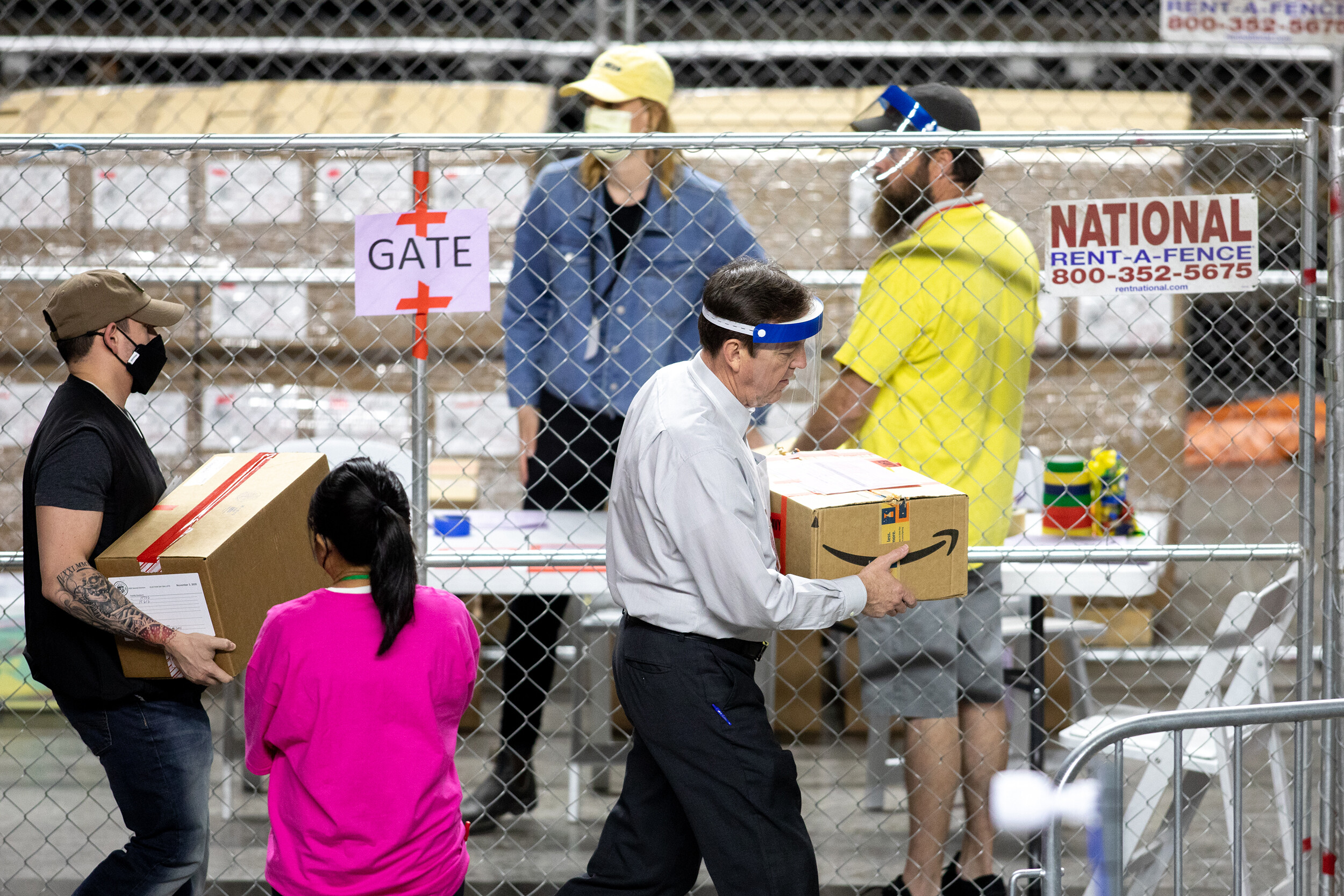 <i>Courtney Pedroza/Getty Images</i><br/>Former Arizona Secretary of State Ken Bennett (right) works to move ballots from the 2020 general election at Veterans Memorial Coliseum on May 1 in Phoenix