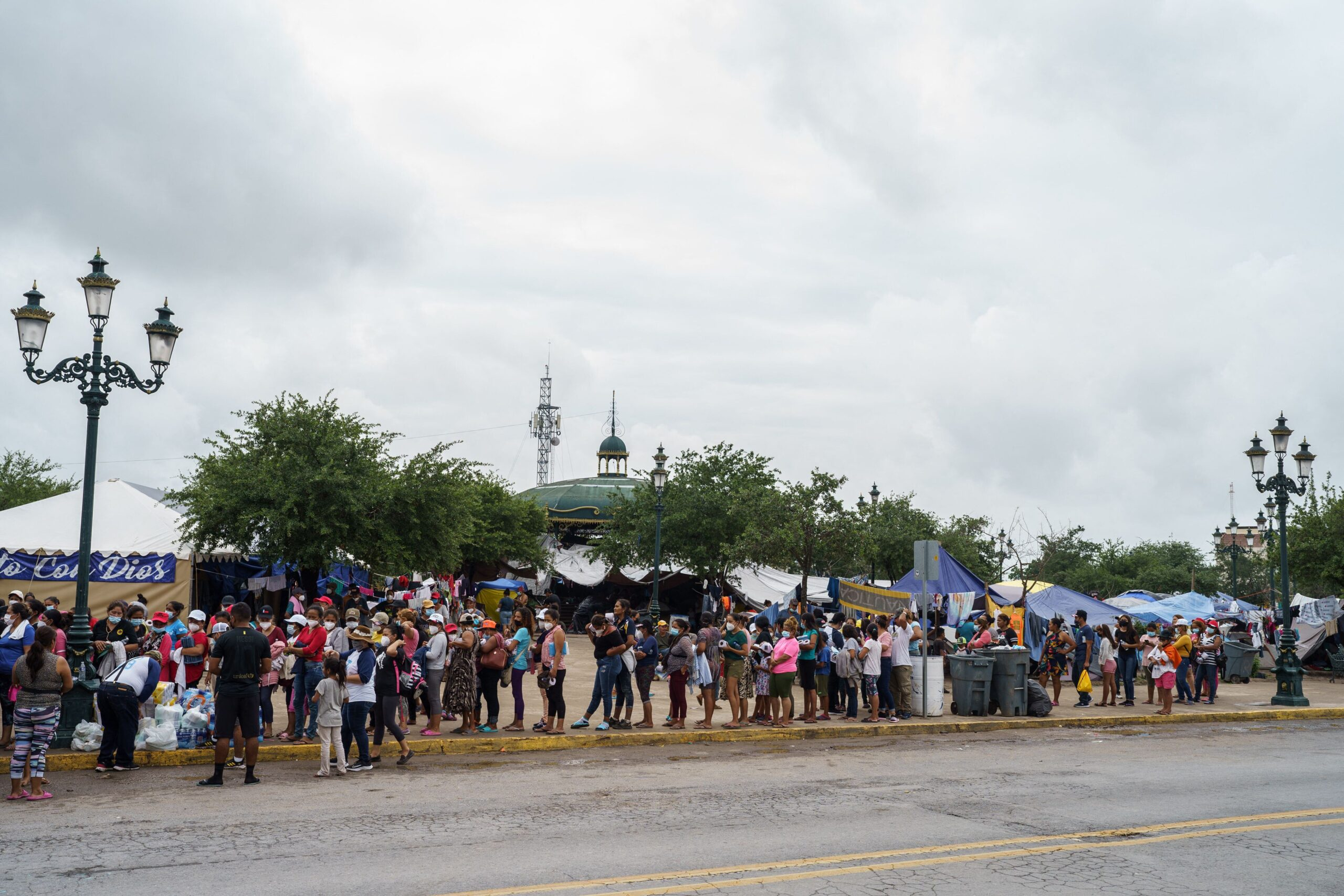 <i>Paul  Ratje/AFP/Getty Images</i><br/>Migrants who were sent back to Mexico under Title 42 wait in line for food and supplies in a camp across the US-Mexico border in Reynosa