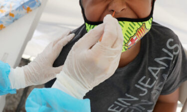 A boy receives a free Covid-19 test at a St. John's Well Child & Family Center mobile clinic set up outside Walker Temple AME Church in South Los Angeles amid the coronavirus pandemic on July 15