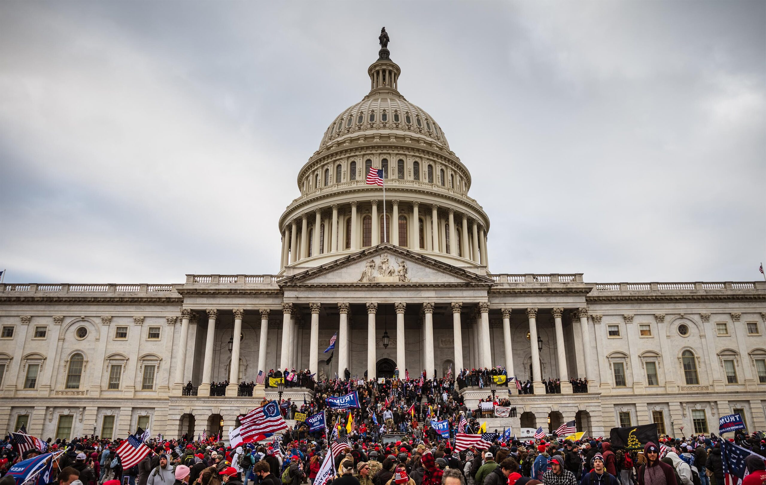 <i>Jon Cherry/Getty Images</i><br/>A large group of rioters stand on the East steps of the Capitol Building after storming its grounds on January 6