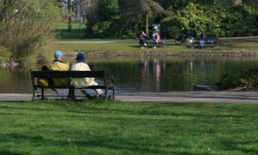 The ultimate niksen: A couple sits on a bench in front of a pond at Wilhelminapark in Utrecht