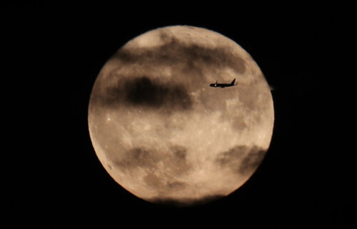 A plane flies past the harvest moon as it rises behind the Statue of Liberty in New York City