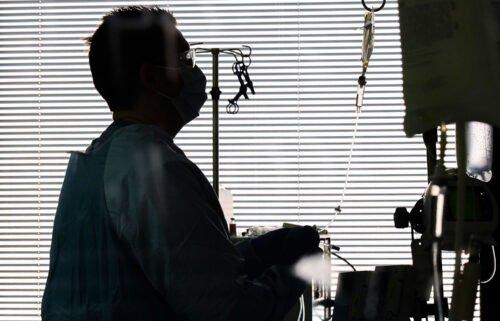 East Alabama Medical Center nurse Harvard Graham checks fluids for a Covid-19 patient in the intensive care unit Thursday