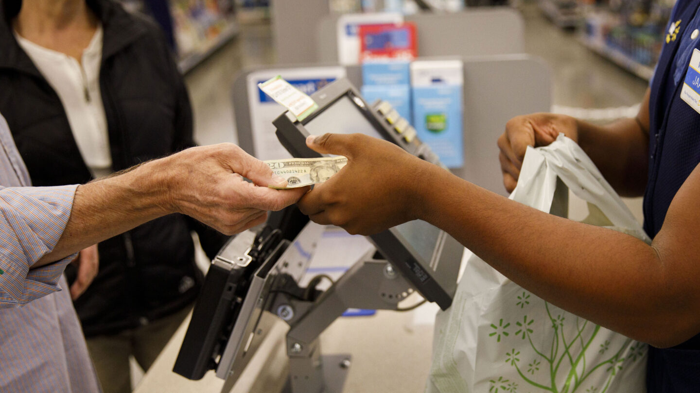 <i>Patrick T. Fallon/Bloomberg/Getty Images</i><br/>A customer hands cash to an employee while making a purchase at a Walmart location in Burbank