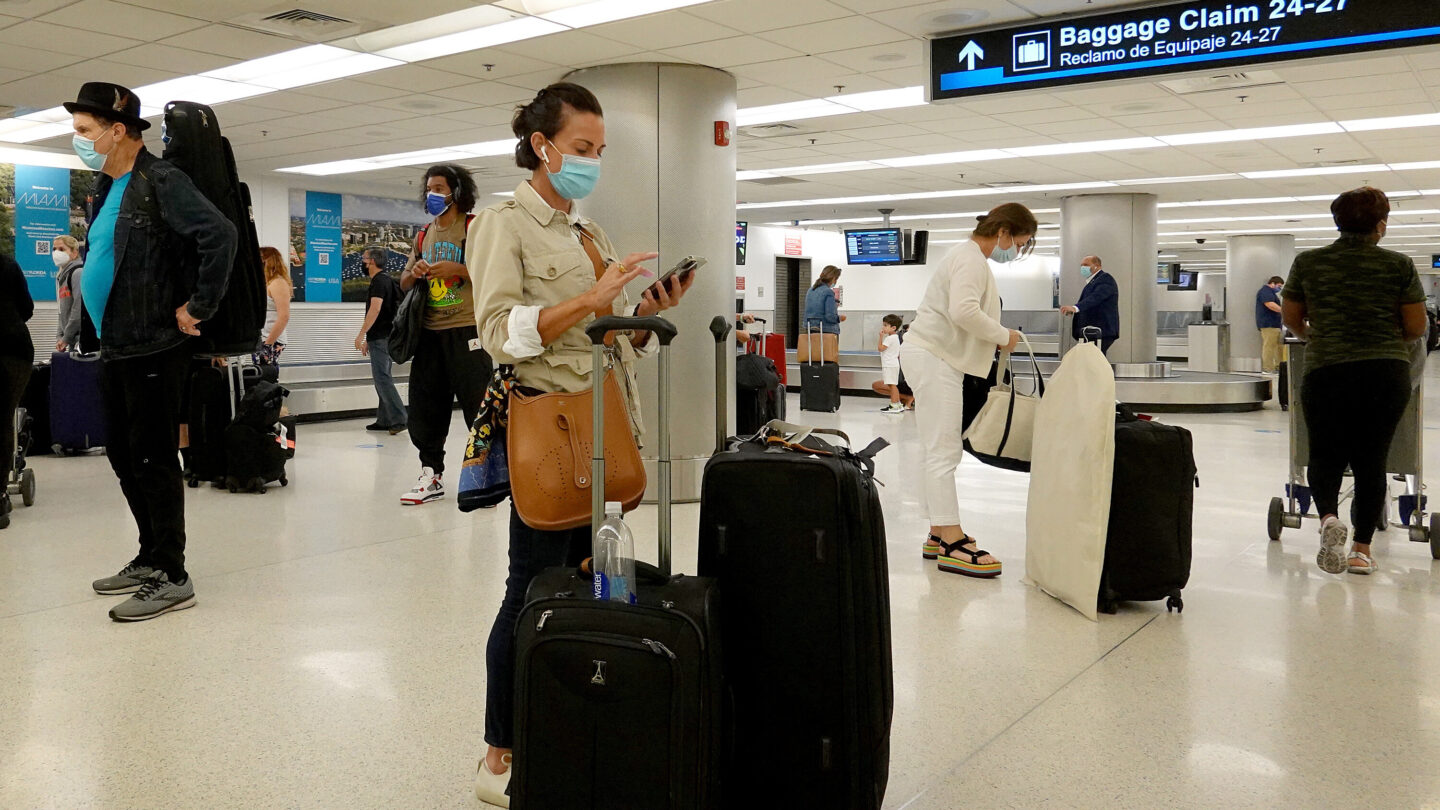 <i>Joe Raedle/Getty Images</i><br/>Travelers gather their luggage as they arrive at Miami International Airport on September 20.