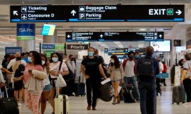 Travelers make their way through the Miami International Airport on September 3 in Miami