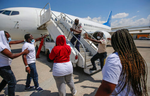 Police officers try to block a deportee from boarding the same plane he and others were deported in.